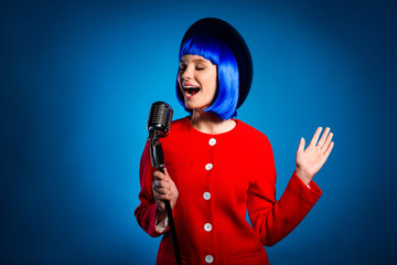 Portrait of creative active artist in headwear red outfit singing with open mouth close eyes in microphone isolated on bright vivid blue background. Comfort relax leisure concept