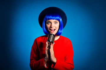 WOW! Portrait of amazed big-eyed artist in headwear red outfit singing in microphone isolated on vivid blue background. Entertainment art broadcasting concept