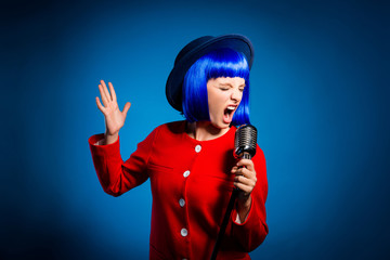 Portrait of professional emotional artist in head wear singing hard rock with wide open mouth and close eyes gesturing with hand isolated on bright blue background. Art jazz opera concept