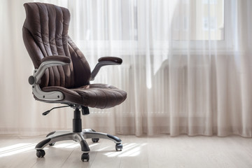 Comfort office chair in the room against window with tulle. Bright background