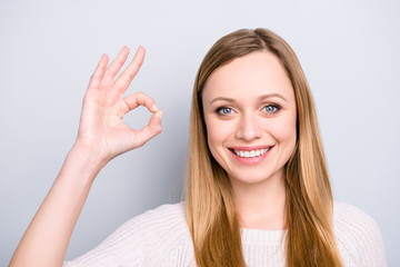 Head shot portrait of positive stylish girl with beaming smile gesturing ok sign with fingers looking at camera isolated on grey background