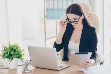 Portrait of smart agent successful business shark trendy woman looking out glasses at screen of laptop holding tablet in hand sitting in modern office with interior