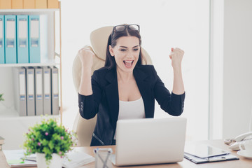 Portrait of cheerful positive attorney holding hands up yelling celebrating big effective results great triumph getting inspiration motivation clenches fists sitting at desktop in modern work place