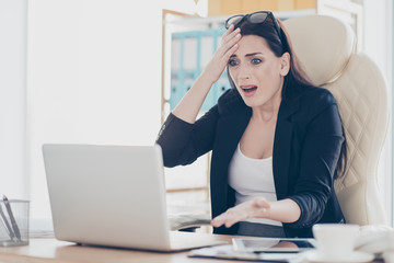 Portrait of shocked stressed woman gesturing with hands at laptop having bad news information sitting in modern workstation