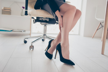 Low angle view cropped portrait of business woman's legs touching with hand enjoying perfect smooth soft skin after lotion moisturizer hydration having injury hurt