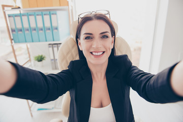 Self portrait of cheerful positive woman with glasses on head shooting selfie on front camera with two hands enjoying break having fun video call with friend
