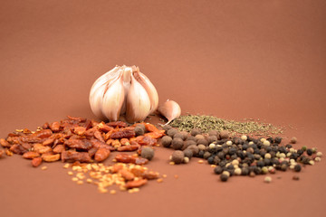 Garlic with spices stock images. Hot peppers and pepper images. Mixture of spices images. Spice mix on a brown background. Aromatic spice collection