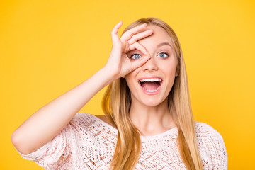 Head shot portrait of toothy positive laughter with open mouth showing ok sign around one eye looking at camera wearing casual outfit isolated on yellow background