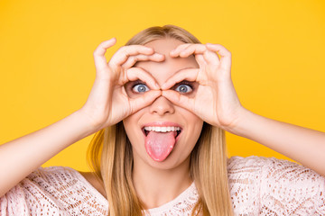 Head shot close up portrait of foolish playful girl gesturing tongue-out making binoculars with ok signs looking at camera isolated on yellow background