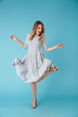 Full length image of Cheerful blonde woman in dress dancing
