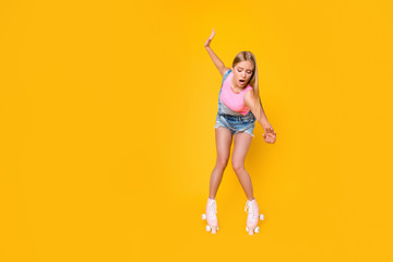 Portrait of nervous depressed girl learning roller skating carefully keeping balance trying not to fall down screaming loud isolated on yellow background