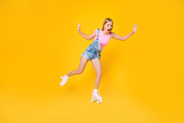Portrait of nervous yelling girl learning roller skating afraid to ride trying not to fall down isolated on yellow background, street outside urban activity concept