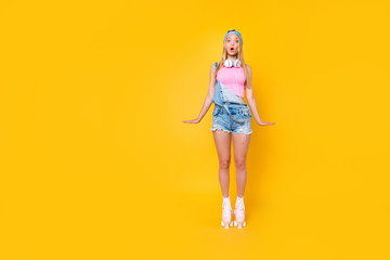 Full body portrait of astonished frustrated chick stressed girl with wide open eyes mouth on roller skates in denim overall isolated on yellow background