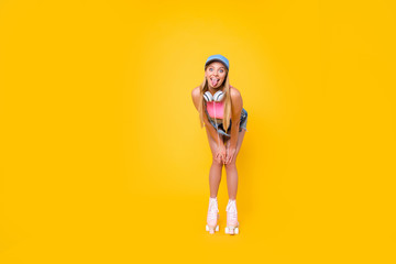 Portrait of comic childish girl on roller skates with headset on neck gesturing tongue out at camera isolated on yellow background