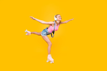 Portrait of cheerful creative joyful girl in jeans overall riding on roller skates listening music using headset making air plane holding hands to the side raised leg isolated on yellow background