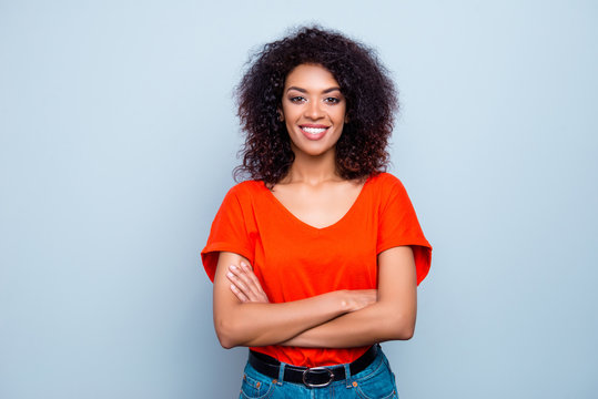 Portrait of cheerful glad woman with white toothy smile plump lips in orange t-shirt holding hands crossed looking at camera isolated on grey background