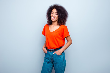 Portrait of joyful cute woman with modern hairdo in bright t-shirt jeans holding two hands in pockets isolated on grey background