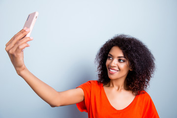 Portrait of cheerful pretty woman with modern hairdo in bright t-shirt shooting selfie on front camera of smart phone having video-call with friend isolated on grey background