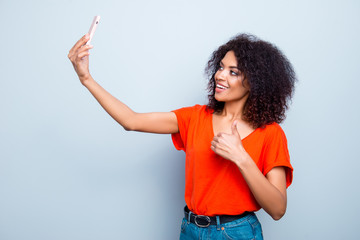 Portrait of cheerful trendy model in vivid outfit with modern hairdo shooting selfie on front camera of smart phone gesturing thumb up like sign with finger isolated on grey background