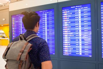 BANGKOK, THAILAND - MAY 30, 2018 : Asian tourist guy looking at schedule at Don Mueang International Airport, Bangkok