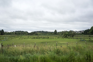 football field outdoors tall bush fence rural