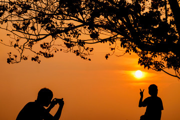 silhouette of happy family father taking daughter photo under the tree in sunset sky.