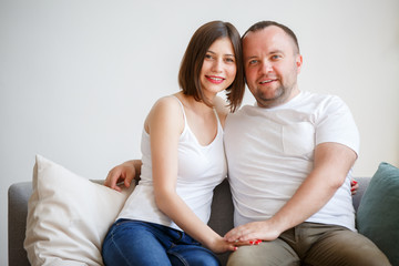 Portrait of young married couple sitting on sofa
