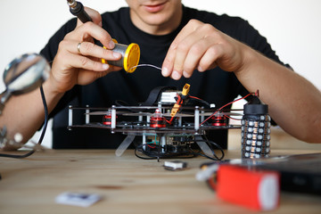 Image of engineer with soldering iron repairing mechanism