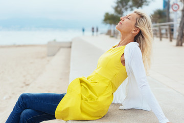 Trendy woman relaxing on a seafront promenade