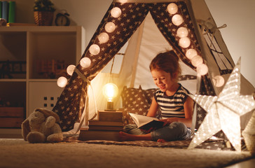 happy child girl laughing and reading book in dark in tent at home