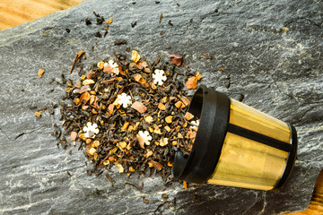 Flavored black tea scattered outside a gold plated tea infuser onto a stone slab.