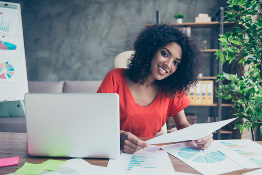 Portrait of pretty trendy woman with beaming smile in vivid outfit sitting at desk in modern office holding document in hand looking at camera. Study education university knowledge concept