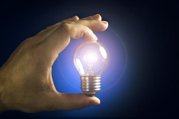 Light bulb in hands on blue background