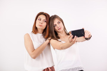 Two happy girls taking a selfie in studio on a white wall