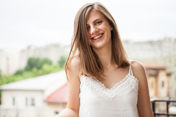 Portrait of a woman with brown hair smiling at camera while sitting at the balcony