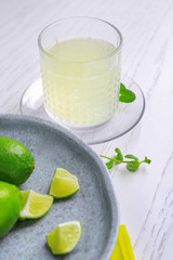 Glass with delicious citrus juice and fresh lime on table
