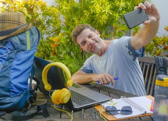 young attractive and happy digital nomad man working outdoors with laptop computer cheerful taking selfie pic with mobile phone