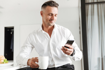 Smiling man dressed in formal clothes having breakfast