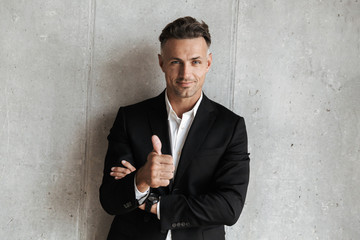 Handsome man dressed in suit showing thumbs up gesture