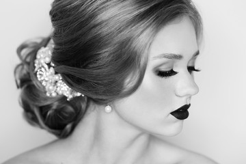 Beautiful young woman with blonde hair decorated with luxurious wedding accessory, pearl earrings and evening makeup. Portrait of attractive female model or bride with elegant hairstyle and red lips.