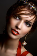 Beautiful girl in a crown and earrings on a dark background. Red dress and red lipstick. Fashion Baroque Style