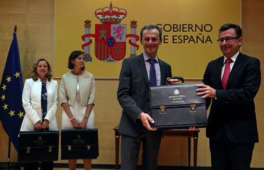 Spain's new Science, Innovation and Universities Minister Duque receives his ministerial briefcase from outgoing Economy Minister Escolano during the taking over ceremony at the Economy Ministry in Madrid