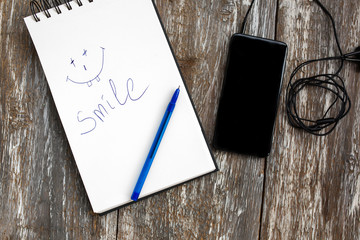 White notebook with a blue pen is lying on the old vintage background. Smile emotions is drawn and written on sketch book. Black smartphone with earphones is lying nearby. Modern technologies.