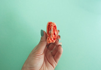 Pink color macaron in woman's hand.