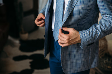 Close-up businessman groom wearing his blue checkered jacket at the morning of wedding day. Concept of men stylish elegance clothes.
