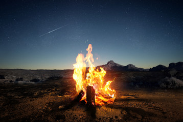 Exploring the wilderness in summer. A glowing camp fire at dusk providing comfort and light to...