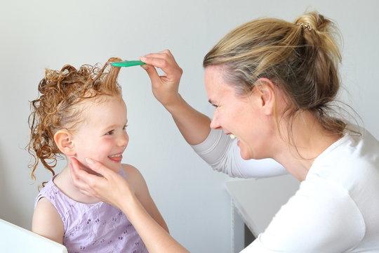 Mutter kämmt mit Läuasekamm Haare der Tochter