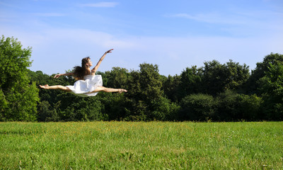 Young beautiful ballerina dancing and jumping in sunny day, nature background of green meadow and forest