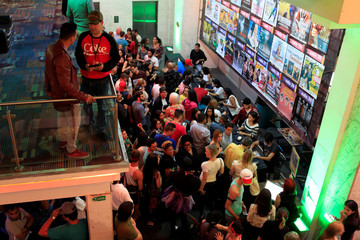 People queue to buy tickets for plays at an improvised theater in an old bingo hall in Caracas