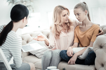 Family problems. Female psychologist holding laptop while appealing mother and daughter talking